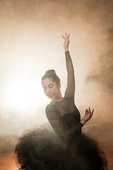 Front view ballerina posing in smoke
