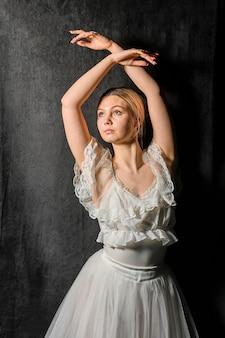 Vista frontale della ballerina che propone con le braccia in su
