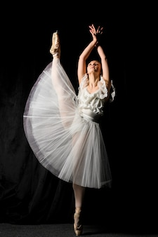 Front view of ballerina in tutu dress with leg up