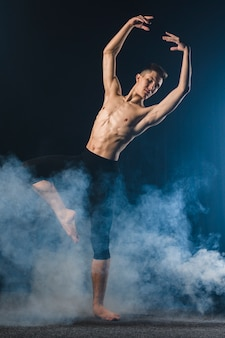 Front view of ballerino in tights posing in smoke