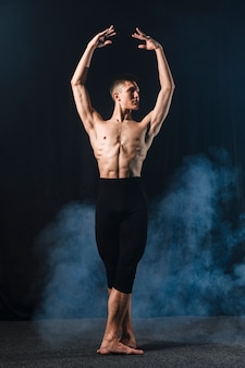 Front view of ballerino in tights and smoke