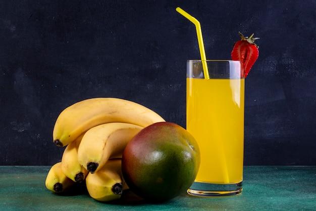 Banane vista frontale con mango e un bicchiere di succo d'arancia