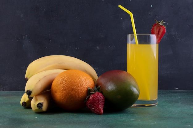 Banane vista frontale con fragole di mango e un bicchiere di succo d'arancia