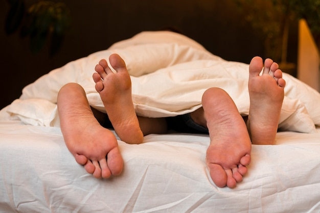 Front view of barefoot couple in bed