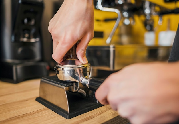 Front view of barista filling cup with coffee for machine