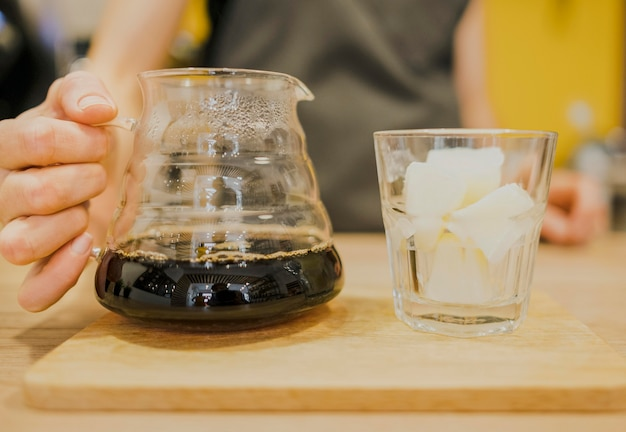 Front view of barista holding coffee pot with glass of ice