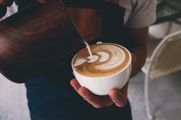 Бариста наливает молоко в чашку кофе, вид спереди