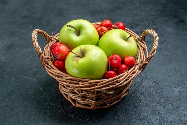 暗い表面のフルーツベリー組成物の鮮度の木にフルーツリンゴと甘いサクランボが入った正面バスケット