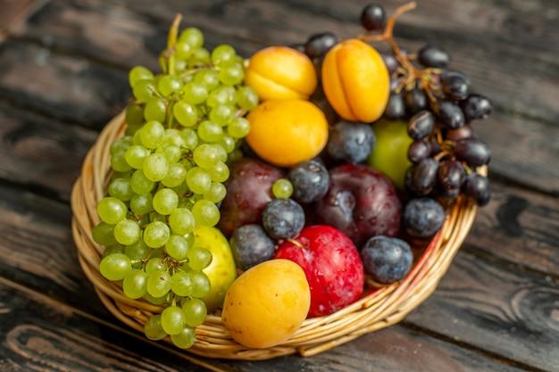 Корзина с фруктами, спелыми и кислыми, такими как виноград, абрикосы, сливы, вид спереди, на коричневом деревенском фоне