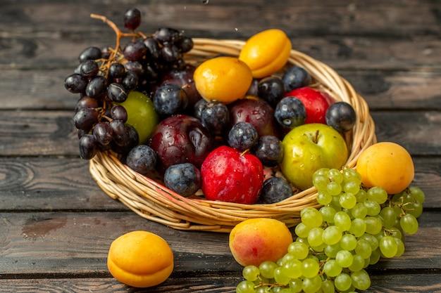 Корзина с фруктами, спелыми и кислыми, такими как виноград, абрикосы, сливы, вид спереди, на коричневом деревенском столе