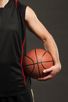 Front view of basketball held by player close to body
