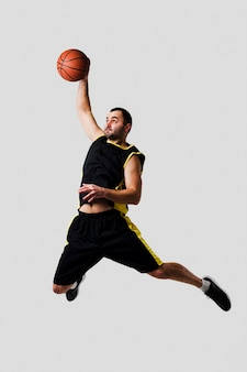 Front view of basketball player caught dunking mid-air