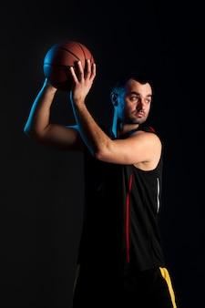 Vista frontale del giocatore di pallacanestro che tiene palla su