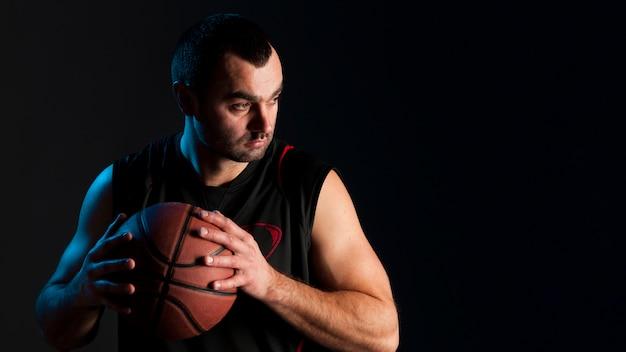 Vista frontale della palla della tenuta del giocatore di pallacanestro con lo spazio della copia