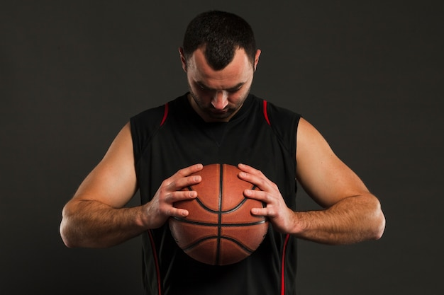 Front view of basketball player posing while looking at ball