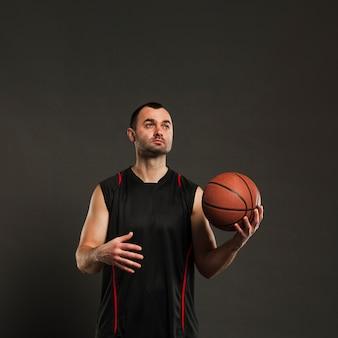 Vista frontale del giocatore di basket in posa mentre si lancia la palla da una mano all'altra