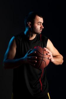 Vista frontale del giocatore di pallacanestro che posa con la palla