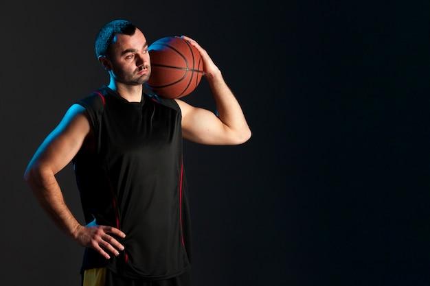 Vista frontale del giocatore di pallacanestro con la palla sulla spalla e lo spazio della copia