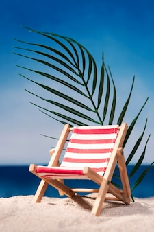 Front view of beach chair on beach with leaf