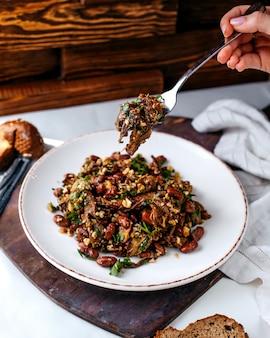 Бобы спереди обжаренные вместе с зеленью внутри белой тарелке на коричневом деревянном столе и коричневом полу