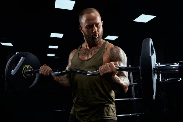 Front view of bearded bodybuilder training biceps with barbell. close up of muscular tattooed sportsman with perfect body posing in gym in dark atmosphere. concept of bodybuilding.