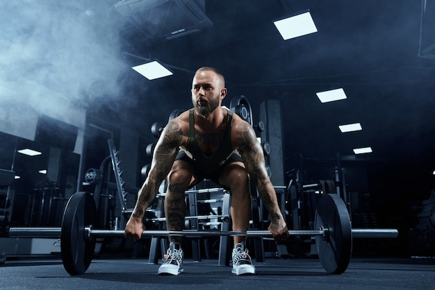 Front view of bearded bodybuilder training legs with barbell.