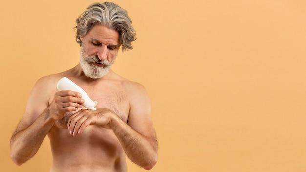 Vista frontale dell'uomo anziano barbuto che applica crema
