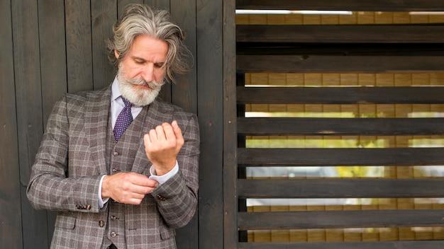 Вид спереди бородатый мужчина позирует в костюме