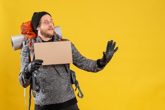Vista frontale di uomo barbuto autostoppista con guanti di pelle e zaino in possesso di cartone vuoto