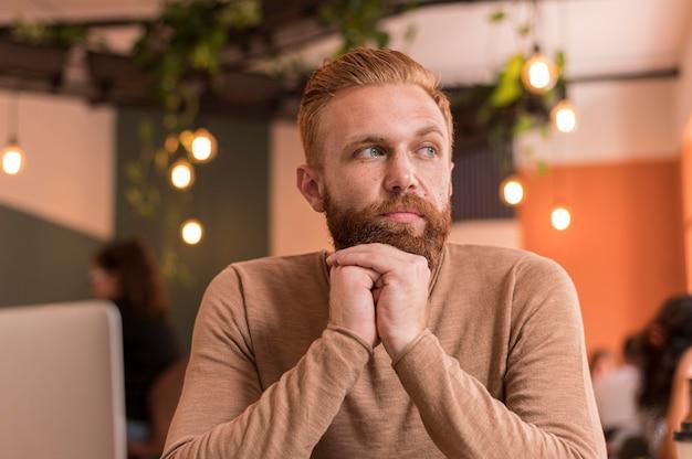 Вид спереди бородатый мужчина смотрит в сторону