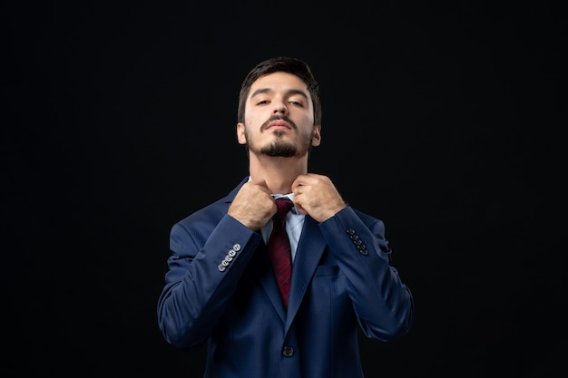 Front view of bearded man in suit straightening his tie and posing on dark wall