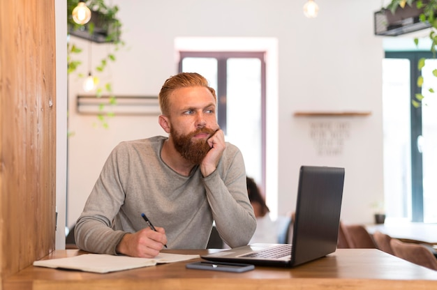 Вид спереди бородатый мужчина делает заметки на работе