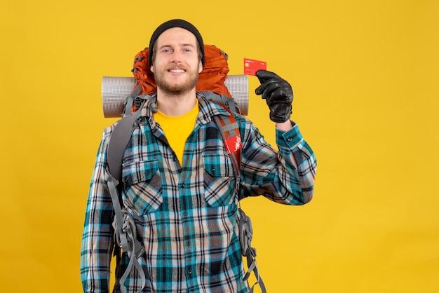 Vista frontale dell'uomo barbuto con zaino in spalla che tiene la carta di credito