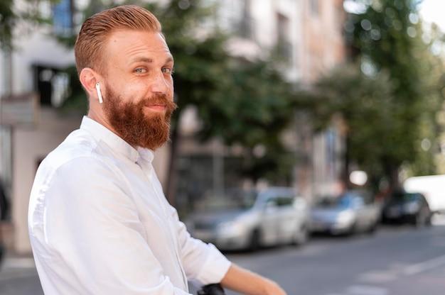 Vista frontale barbuto uomo moderno utilizzando auricolari con copia spazio