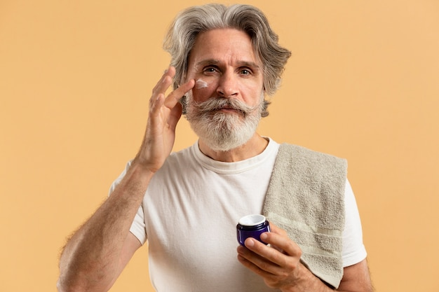 Vista frontale dell'uomo senior barbuto che applica idratante
