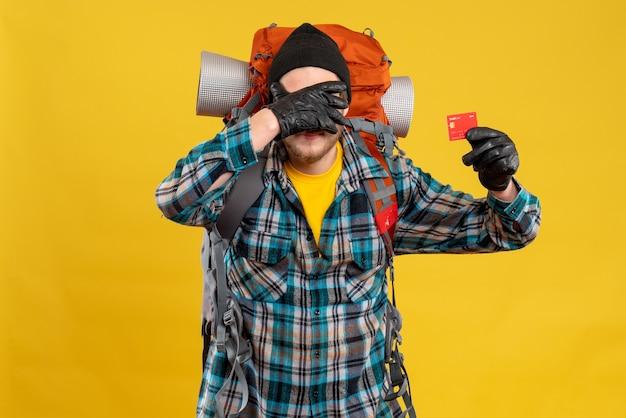 Vista frontale del giovane barbuto con zaino in spalla che tiene la carta di credito che copre il viso con la mano