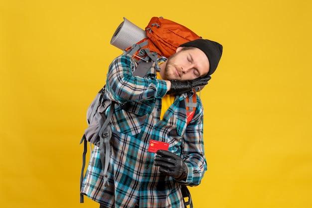 Vista frontale del giovane barbuto con il sonno della carta di credito della holding del viaggiatore con zaino e sacco a pelo