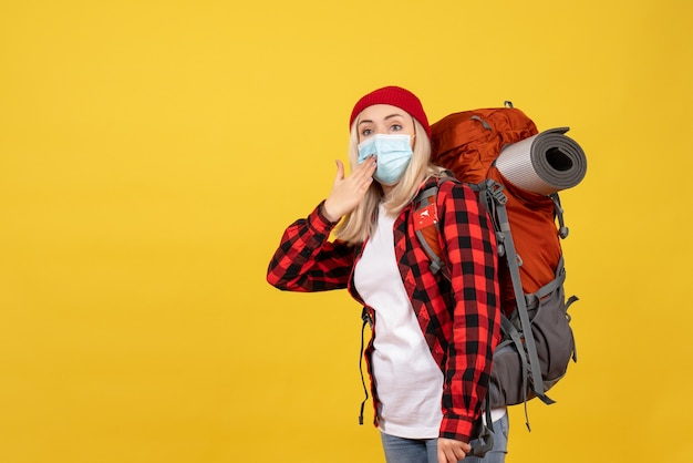Вид спереди красивая блондинка с рюкзаком, стоящим на желтой стене