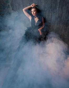 Vista frontale della bella bruna in un vestito nero tutto in fumo in posa sullo sfondo del muro