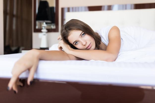 Vista frontale della bella ragazza castana che si trova sotto la coltre bianca in camera da letto. affascinante signora che guarda l'obbiettivo e sorridente mentre riposa a letto. concetto di bellezza, mattina e comfort.