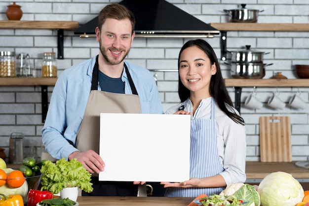 Front view of beautiful couple showing white empty paper in kitchen