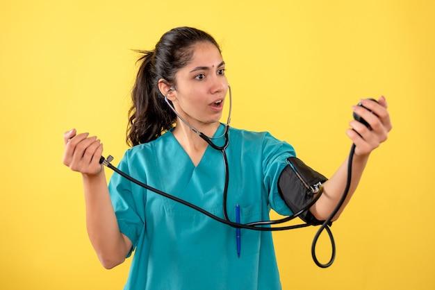 黄色の背景の上に立っている血圧計を保持している制服を着た美しい女性医師の正面図