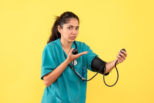 Vista frontale bella dottoressa in uniforme che tiene sfigmomanometri su sfondo giallo