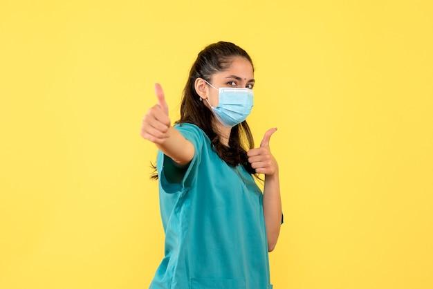 Vista frontale bella dottoressa in uniforme che fa pollice sul segno in piedi su sfondo giallo