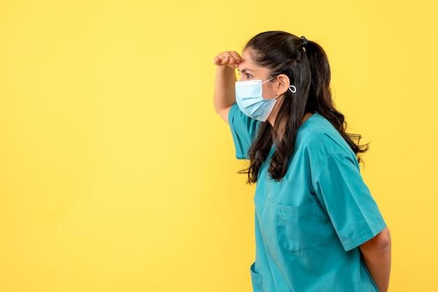 Vista frontale bella dottoressa in uniforme osservando su sfondo giallo