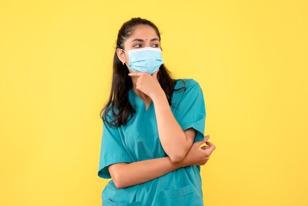 Vista frontale bella dottoressa in uniforme mettendo la mano al mento in piedi su sfondo giallo