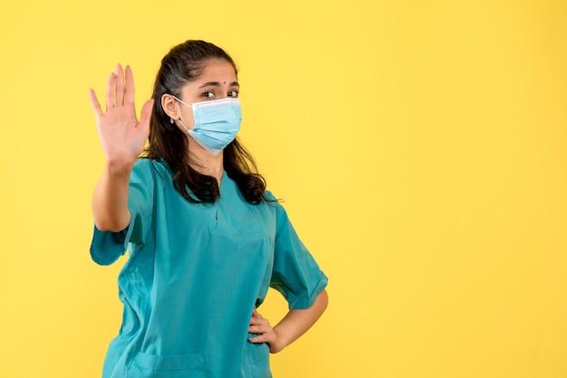 Vista frontale bella dottoressa in uniforme mettendo la mano su una vita in piedi su sfondo giallo