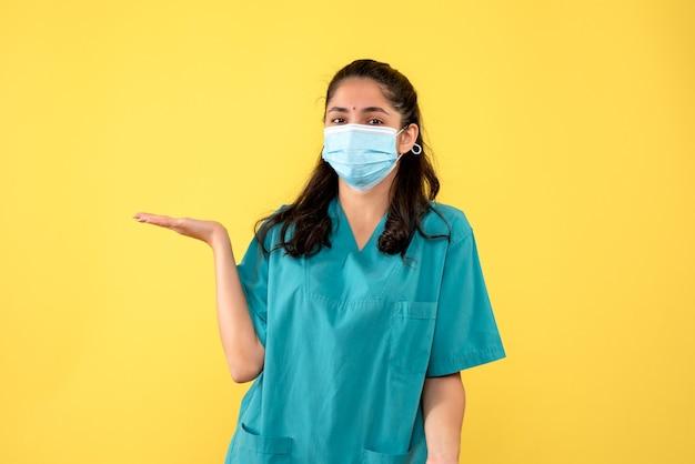 Vista frontale bella dottoressa in uniforme alzando la mano in piedi su sfondo giallo
