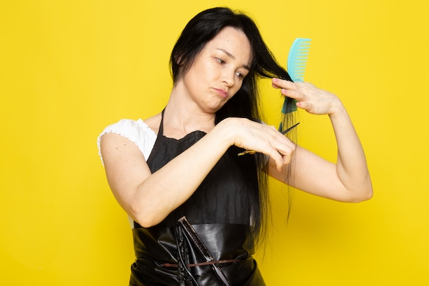 A front view beautiful female hairdresser in white t-shirt black cape with brushes with washed hair brushing and cutting her hair posing on the yellow background stylist barber hair
