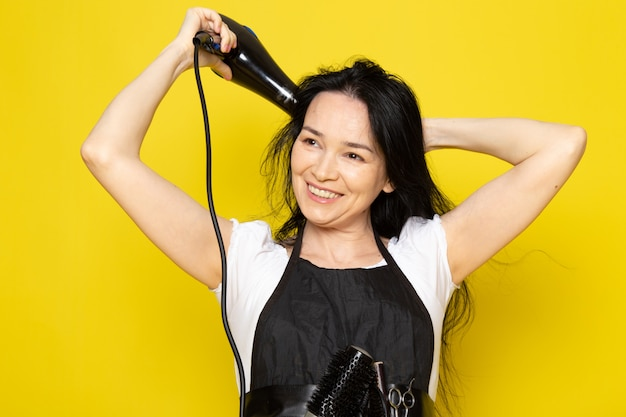 A front view beautiful female hairdresser in white t-shirt black cape with brushes with washed hair drying her hair posing smiling on the yellow background stylist barber hair